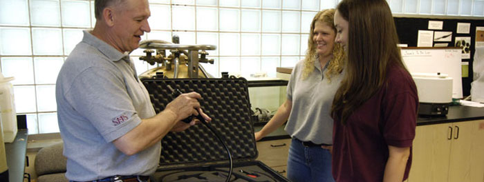 Professor showing a student equipment